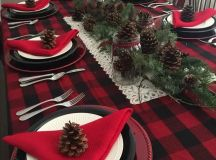 a plaid tablecloth, red napkins and lots of pinecones and evergreens for a rustic tablescape