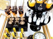 a brass bar cart with glitter bottles, fringe cupcake toppers and a glitter clock