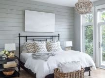 a rustic bedroom with a gla feel and a large basket at the foot of the bed for storing pillows