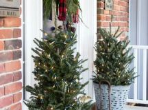 lit up Christmas trees in buckets will make your farmhouse porch cooler