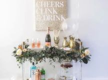 a chic bar cart decorated with a greenery garland and blooms and gold pineapple ice holders