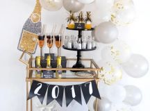 a copper bar cart with white and grey balloons, a banner and glitter bottles and glasses