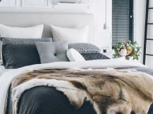 stylish grey, white and black bedding, faux fur and a chunky knit pillow