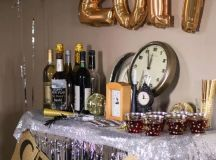 a drink station decorated with silver fringe, a glitter garlands, gold balloons and disco balls