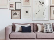a modern living room with a whole gallery wall over the dusty pink sofa