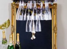 a glass and stirrers chandelier over the bar cart will make the drink station cooler