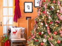 a large Christmas tree decorated with red and white ornaments and plaid ribbons