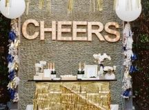 a drink station with gold fringe, gold fringe garlands and marquee lights