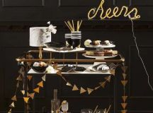 a simple black bar ccart decorated with a gold foil triangle garland and a neon sign