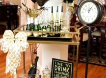 a stylish drink bar cart in black and gold with black and gold balloons and a large bow