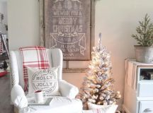a vintage Christmas sign topped with a snowy evergreen garland