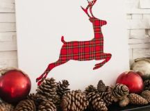 a simple white sign with a plaid deer plus red ornaments and pinecones for a cool mantel