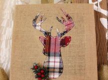 a burlap sign with a plaid deer, faux greenery and berries looks rustic and creative