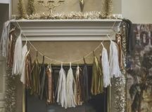 a metallic tassel garland over the fireplace and tinsel garlands