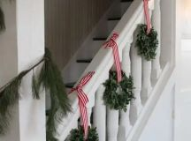 little boxwood wreaths with red and white striped ribbon for staircase decor