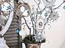 a vintage vase with moss and branches decorated with snowflakes, ornaments and clocks