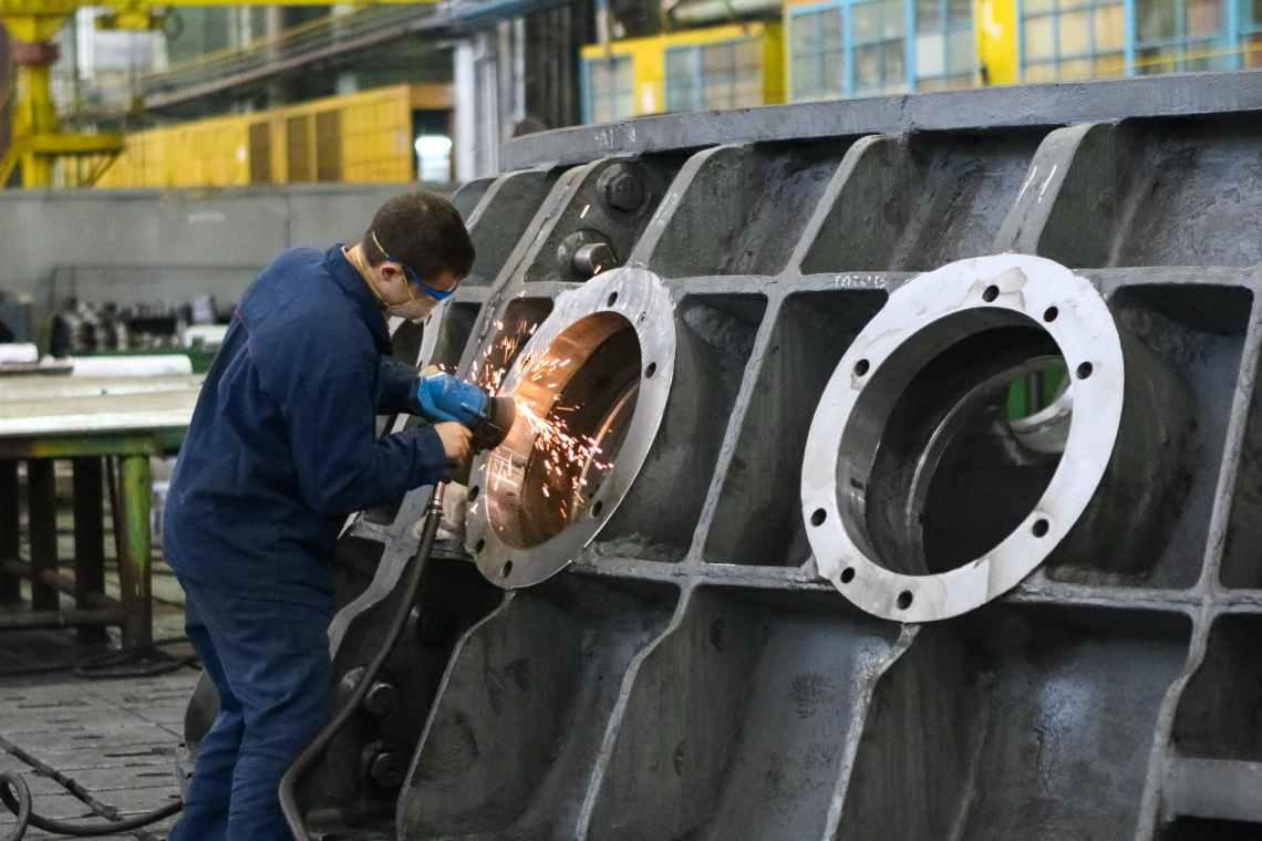 man welding round window frame