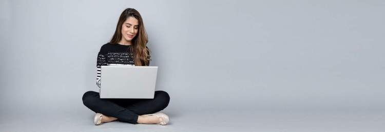 A woman working on her laptop - write for us
