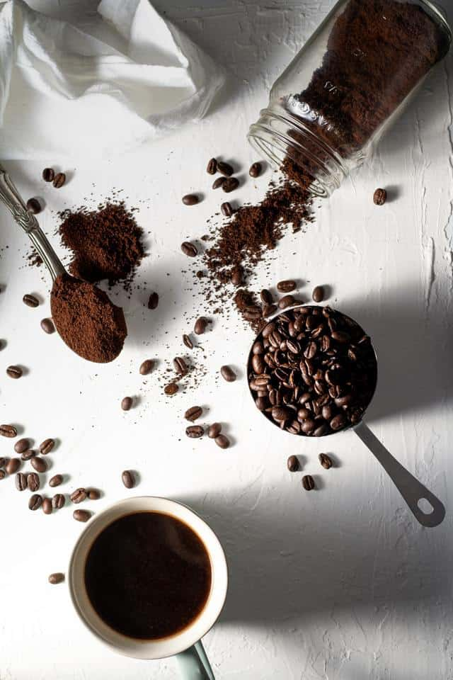 coffee beans, ground coffee, and a cup of brewed coffee