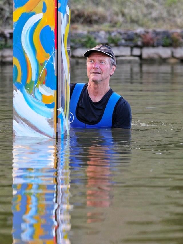 Kevin Pearsh dans l'eau près de l'un de ses totems