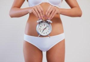 אשה המחזיקה שעון מול הבטן