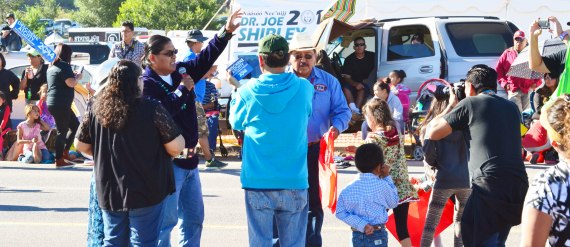 Navajo Nation presidential candidate Chris Deschene, who is holding a microphone and waving, received loud applause and shouts of support from people of all ages during the 68th annual Navajo Nation Fair parade in Window Rock, Ariz., on Sept. 9, 2014. KTNN 660 AM radio station interviewed Deschene in front of the Window Rock headquarters of political opponent Joe Shirley Jr. (Photo by Marley Shebala. Please give proper credit when re-using photo.)