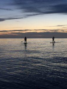 Two people paddling at sunset Photo by John Manelos www.fairhopepaddleboard.com