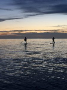 Two people paddling at sunset Photo by John Manelos www.fairhopepaddleboard.com