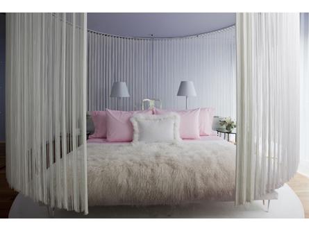 dormitorio blanco con cojines rosas y flecos