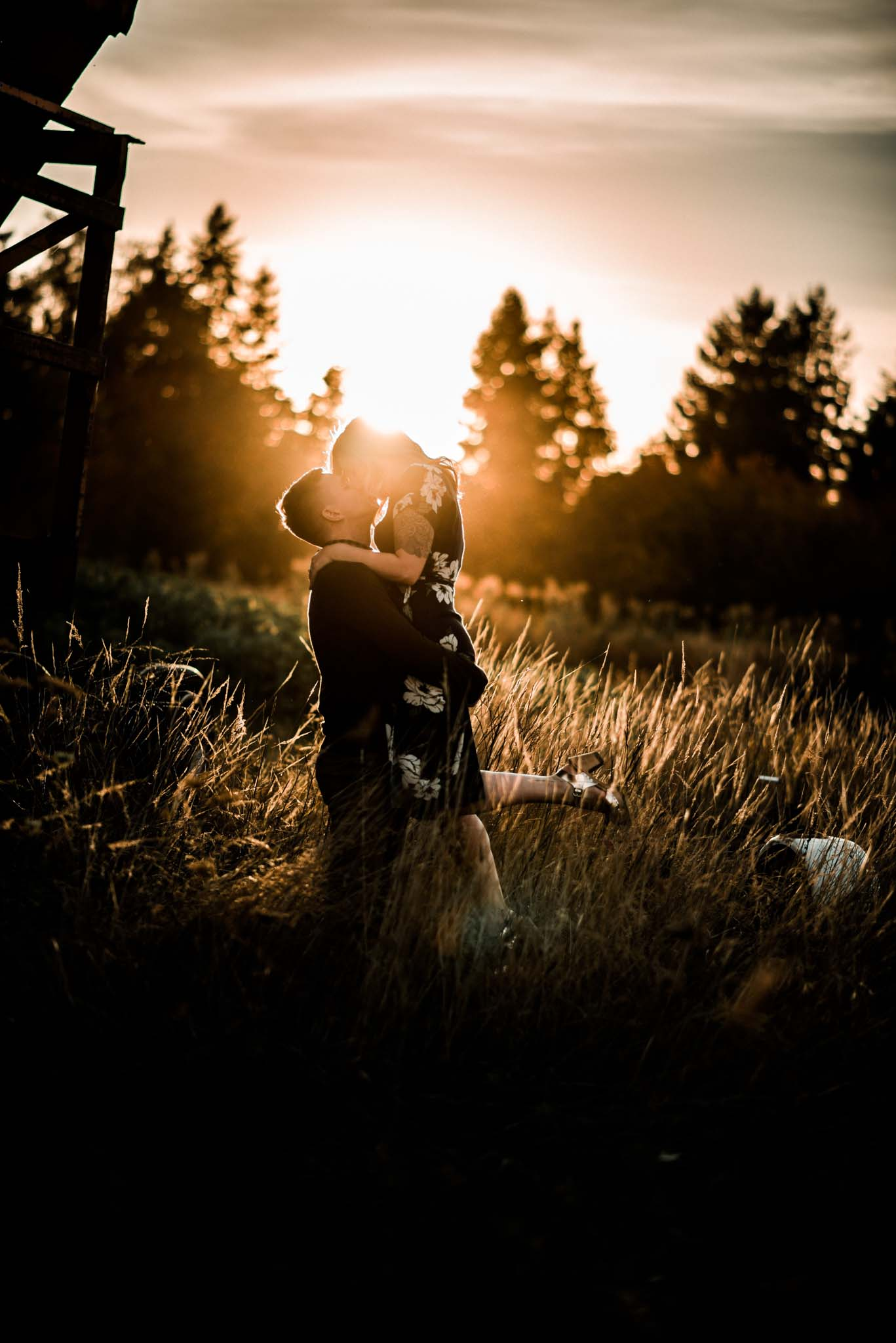 Engaged couple holding each other during sunset in the middle of a field and pumpkin patch