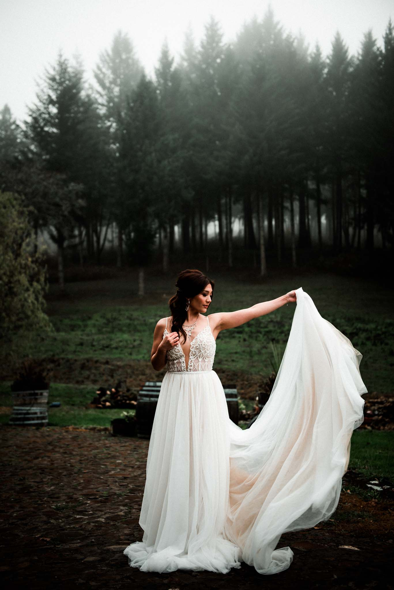 Bride portrait dancing in her gown outdoors during a foggy winter day at the Maysara Winery Oregon