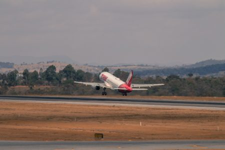 white and red airplane in a runway