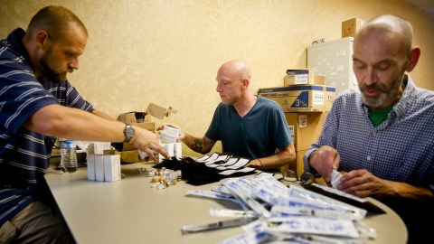 Lawson Koeppel, executive director and co-founder of Virginia Harm Reduction Coalition, center, assembles naloxone kits, which contain the opioid overdose reversing drug. Volunteers Christopher Wagner and Charles Fisher help load the kits before taking them out into the community. The group is committed to preventing overdose deaths in Roanoke. (Photo by Stephanie Klein-Davis for Direct Relief)