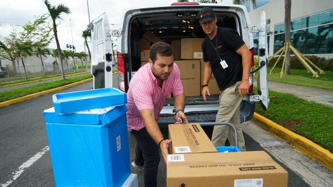 Direct Relief's Andrew MacCalla and Ruben Bras of the Puerto Rico Primary Care Association load a cold shipping container full insulin donated by Eli Lilly into a van for transport to a San Juan primary care clinic. (Lara Cooper/Direct Relief)