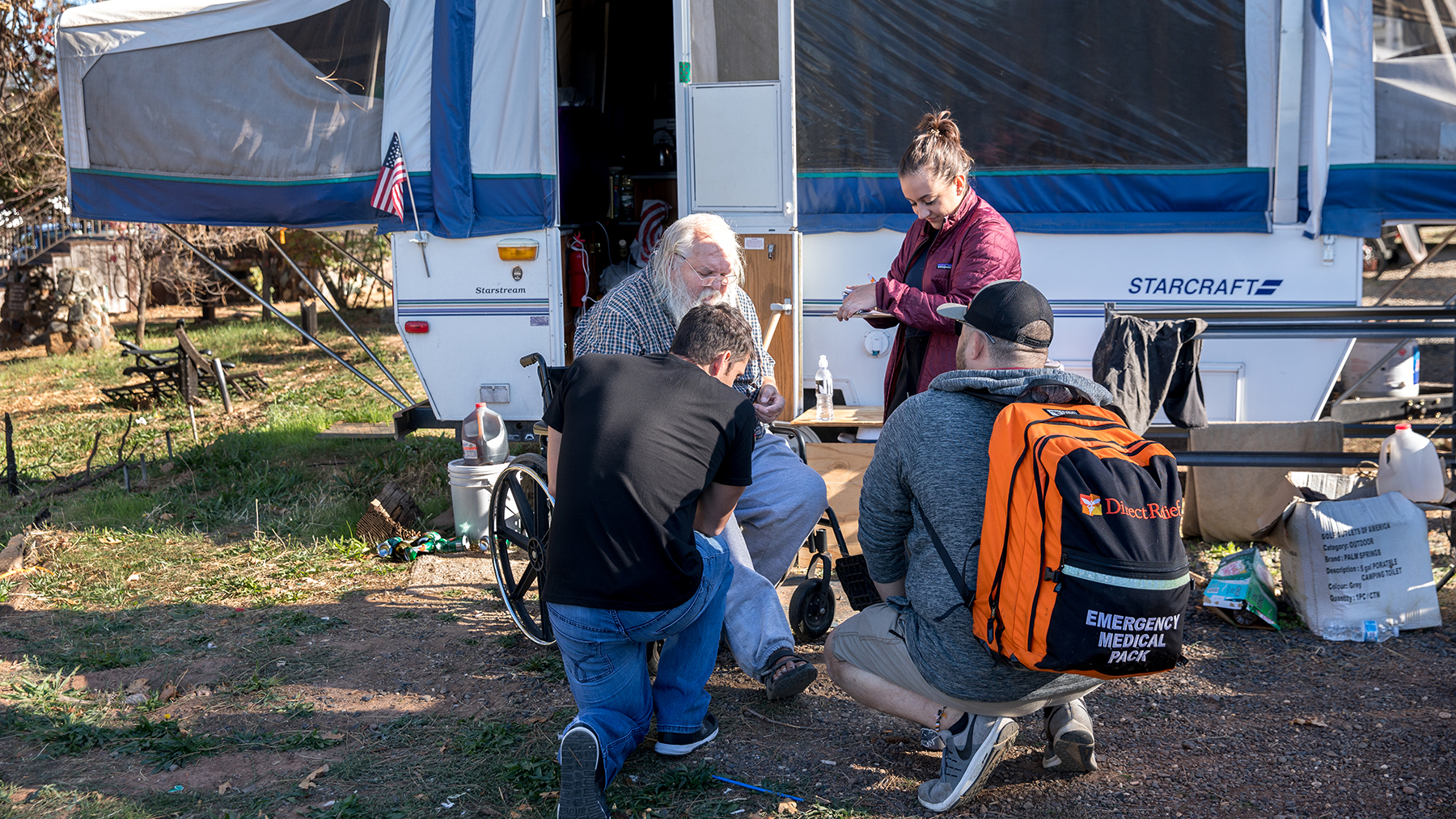 "Paramedics Steve Caput and Sean Biswun, along with Medspire secretary Katie Rosauer, attend to Charles ""Chip"" Baniewski outside his RV. (Mark Semegen for Direct Relief)"