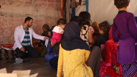 A Syrian American Medical Society health worker provides care to women and children outside of hospital walls in Syria. Many medical facilities have been targeted by missiles, and care must often take place elsewhere for safety reasons. (Photo courtesy of SAMS)