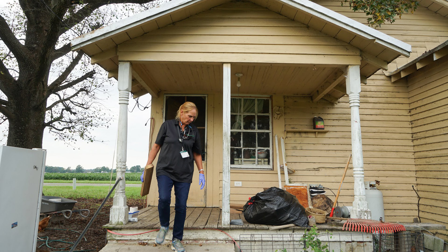 Nurse Gena Byrd, who does medical outreach for local farmworkers for Green County Health Care, at the home of an elderly patient in Snow Hill, North Carolina. The home of the homebound woman had recently flooded as a result of Hurricane Florence, and Byrd and other staff, as well as volunteers, were working on the home. (Lara Cooper/Direct Relief)