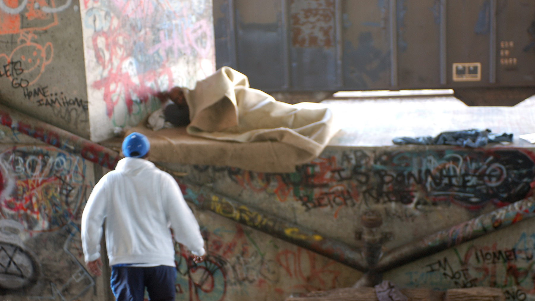 A health worker approaches a sleeping man. (Photo courtesy of NHCHC)