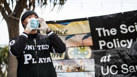 Jamal Trulove calls out to people passing by on Fillmore Street in San Francisco to let them know they are giving away free hand sanitizer and face masks. (Photo Courtesy of Tru Narrativ)