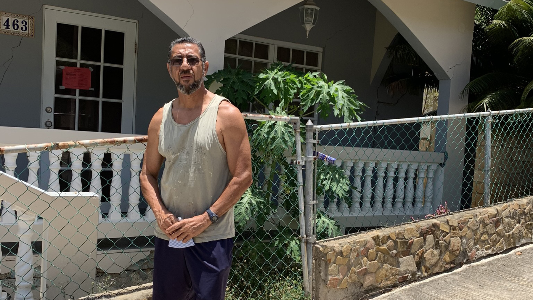 William Ducós poses outside his damaged house. (Direct Relief photo)