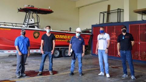 Los bomberos de la estación de bomberos en Cataño, Puerto Rico, y un miembro del personal de Direct Relief examinan los paneles solares recién instalados en el techo de la estación. (Ana Umpierre /Direct Relief)