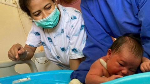 A midwife demonstrates the proper technique for bathing a baby. (Photo courtesy of Bumi Sehat)