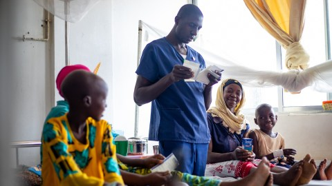 19 April 2021 - Muhimbili National Hospital, Paediatric Block, Dar es Salaam, Tanzania - Joyna Paul (L), a young cancer patient with her mother, Rehema Mganule, and Warda Bashiru (R), a young cancer patient with her mother, Lukia Salmo, receiving medication from a nurse, Stephano Athanas, at one of the childrens wards.