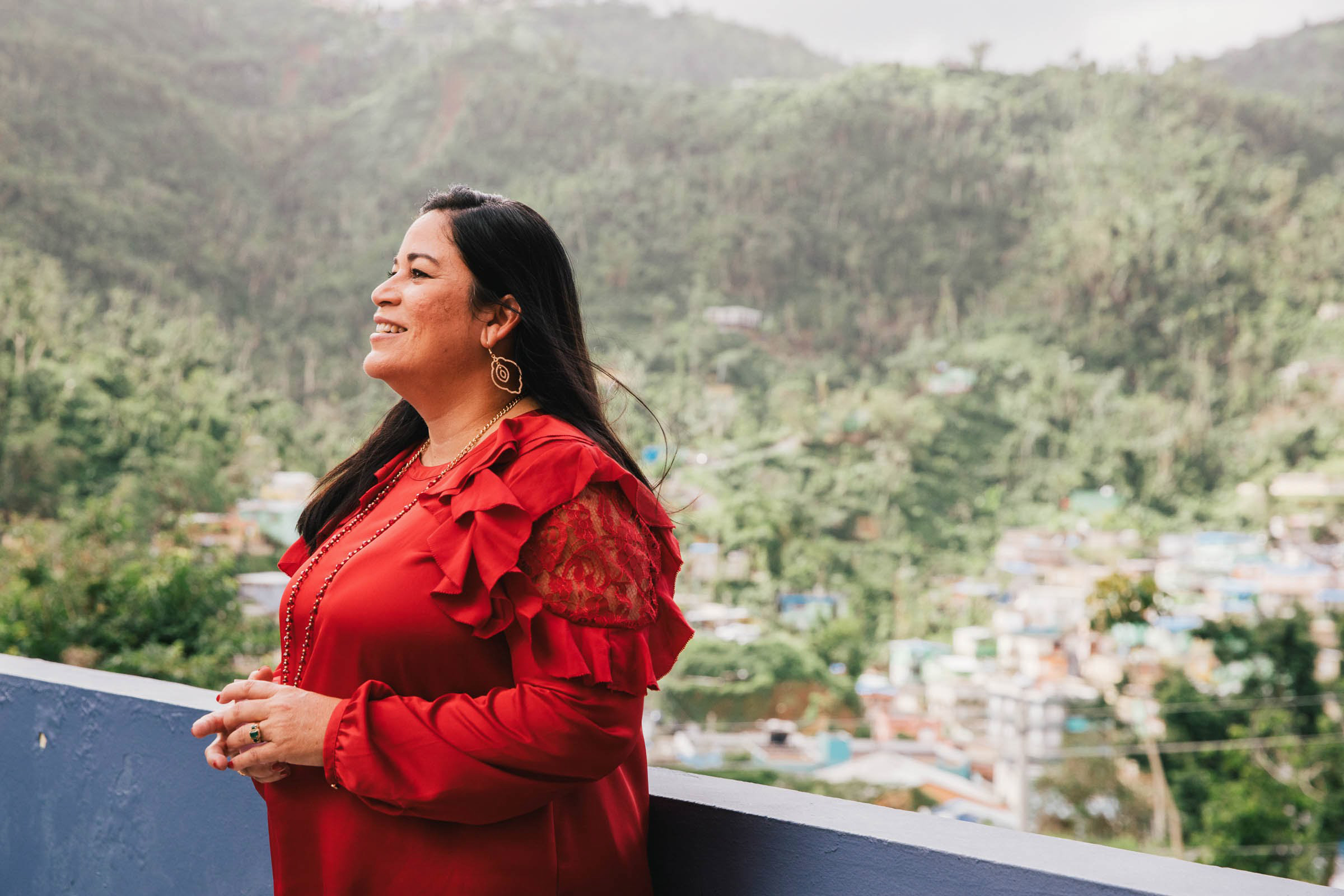 """Gloria del C. Amador Fernández, executive director of Salud Integral de la Montana Health Center, overlooks the mountain community of Naranjito on Dec. 17, 2017. During Hurricane Maria's high winds, the health center stayed open. """"We were the only ones providing care on the mountain,"""" she said. (Photo by Donnie Hedden for Direct Relief)"""