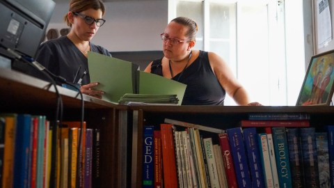 Dr. Carla Rossotti and Lisel Vargas talk through a patient's file inside a children's library turned medical clinic. (Lara Cooper/Direct Relief)