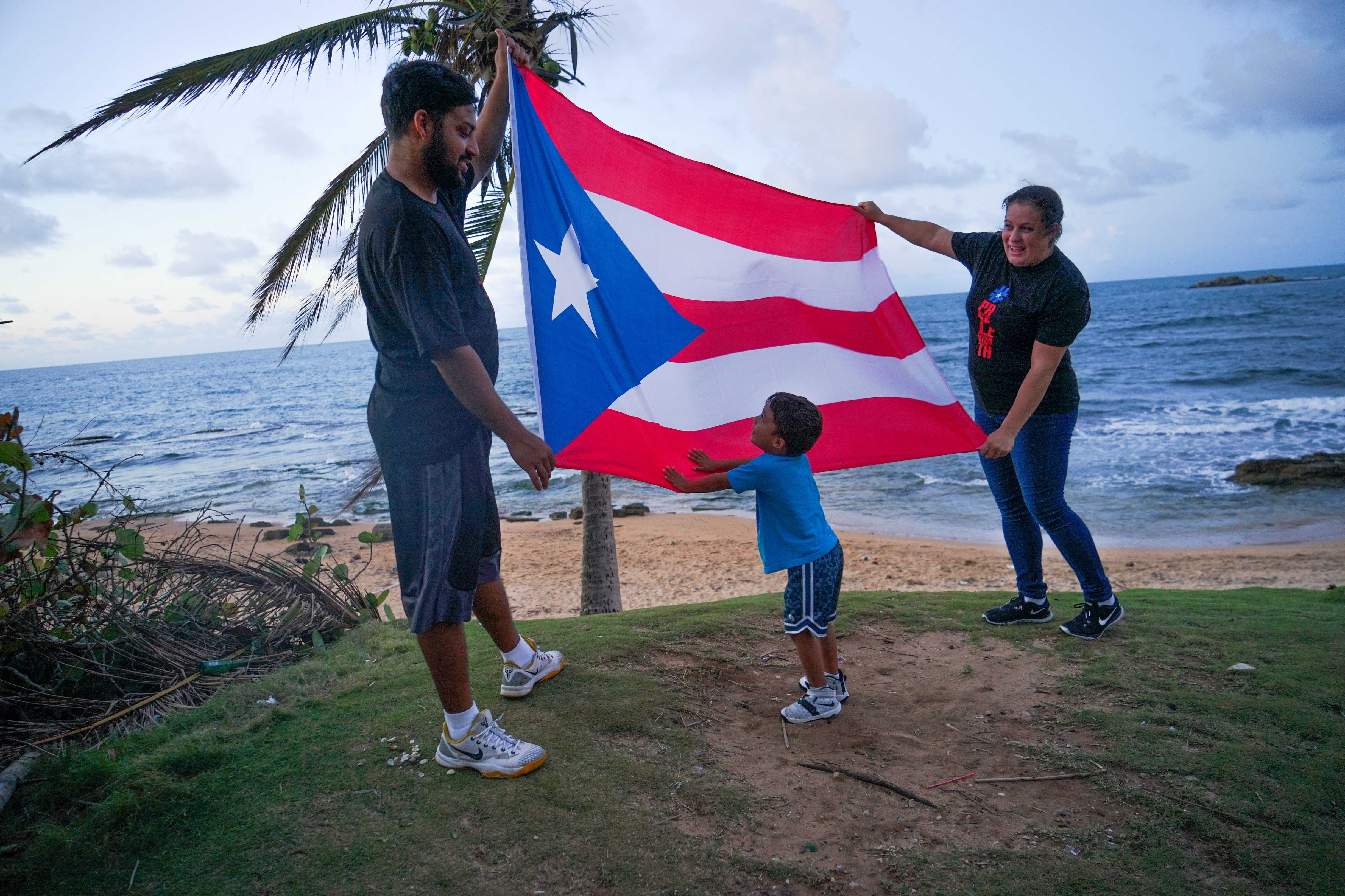 A boy and his family play on the beach in Loiza, Puerto Rico. (Lara Cooper/Direct Relief)