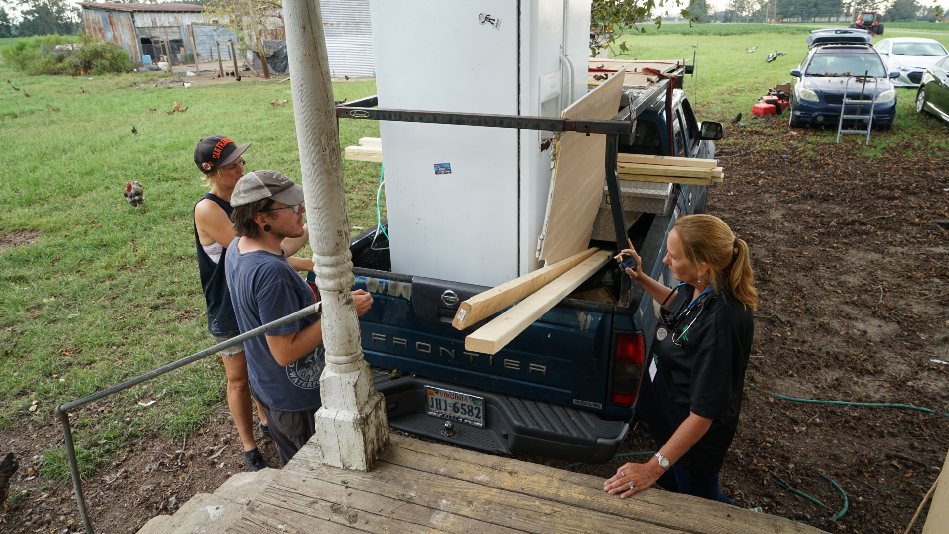 Nurse Gena Byrd (right), who does medical outreach for local farmworkers for Green County Health Care, coordinates with volunteers to move a new refridgerator into the home of an elderly patient in Snow Hill, North Carolina. Byrd often goes above and beyond for local patients. (Lara Cooper/Direct Relief)
