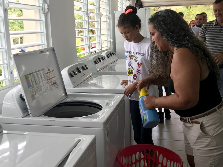 Families do laundry on Friday, June 22, 2018, at the opening of a solar laundry facility in Yabucoa, Puerto Rico. Solar laundries are now operating in Orocovis, Utuado and Yabucoa. (Photo by Maylin De Leon for Direct Relief)