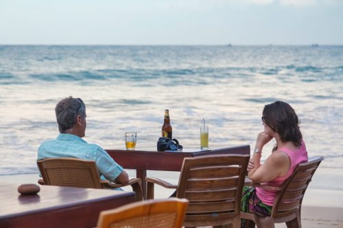 Tourist couple having drink at beach bar. Unawatuna is a major tourist attraction in Sri Lanka famous for its beautiful beach and corals.