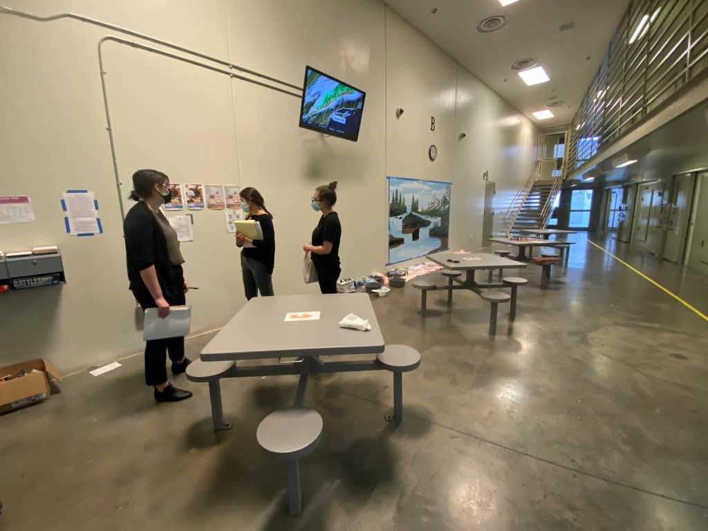 Room with high ceiling and concrete grey floors and white walls. A couple of long gray tables with benches are in the middle of the room. Three people stand near wall wearing dark colored clothing.